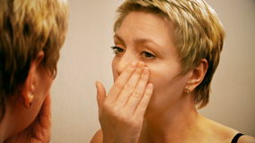 Woman applies make-up concealer foundation cream stock footage