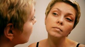 Woman applies make-up concealer foundation cream stock video