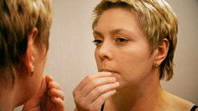 Woman applies make-up concealer foundation cream stock video footage