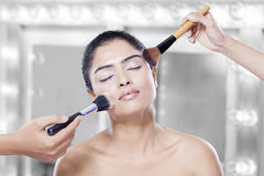 Woman apply cosmetics on her cheek Stock Photo