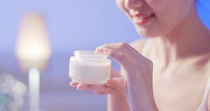 Woman apply cream with face. Beauty woman apply cream with face on the bed at night stock photo