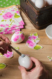 Woman apply glue on colored Easter egg. decoupage Stock Photos