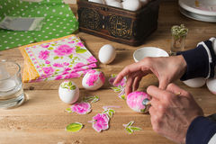 Woman apply glue on colored Easter egg. decoupage Stock Images