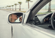 Woman apply  lipstick looking in rear view car mirror Stock Photo