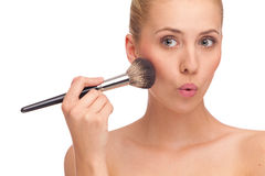 Woman apply powder on a cheek and makes funny face. Royalty Free Stock Image
