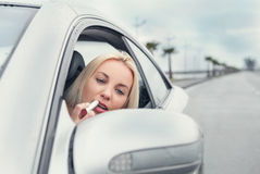 Woman apply rose lipstick looking in car mirror Royalty Free Stock Photo