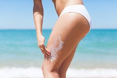 Woman apply sunscreen lotion on hip legs stock images