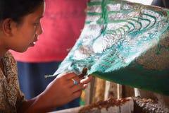 Woman apply wax for batik making stock photography