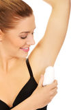 Woman applying antiperspirant. Stock Photo