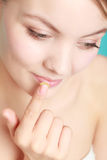 Woman applying balsam for lips Stock Photography