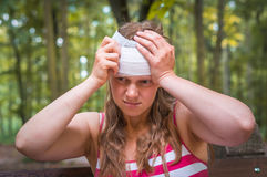 Woman applying bandage on her head after injury in nature. Woman applying compression bandage on her head after injury in nature stock images