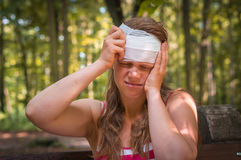 Woman applying bandage on her head after injury in nature. Woman applying compression bandage on her head after injury in nature stock photography