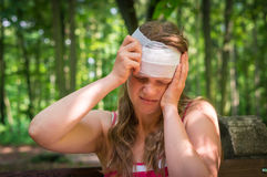 Woman applying bandage on her head after injury in nature. Woman applying compression bandage on her head after injury in nature royalty free stock images