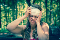 Woman applying bandage on her head after injury in nature. Woman applying compression bandage on her head after injury in nature - retro style stock photo