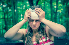 Woman applying bandage on her head after injury in nature. Woman applying compression bandage on her head after injury in nature - retro style stock image
