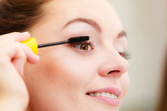 Woman applying black eye mascara to her eyelashes. Woman face eyes painting. Girl applying black eye mascara to her eyelashes looking in bathroom mirror. Makeup stock images