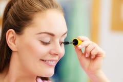Woman applying black eye mascara to her eyelashes. Woman face eyes painting. Girl applying black eye mascara to her eyelashes looking in bathroom mirror. Makeup stock image
