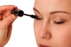 Woman applying black mascara on eyelashes, doing makeup. Royalty Free Stock Photography