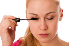 Woman applying black mascara on eyelashes, doing makeup. Royalty Free Stock Image
