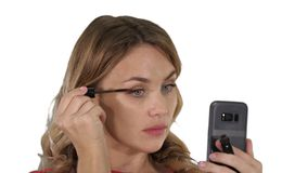 Woman applying black mascara on eyelashes looking in her phone on white background. stock image