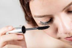 Woman applying black mascara on eyelashes with makeup brush Royalty Free Stock Photo