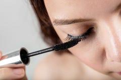 Woman applying black mascara on eyelashes with makeup brush Royalty Free Stock Photography