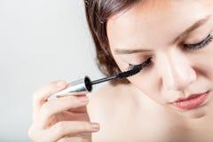 Woman applying black mascara on eyelashes with makeup brush Royalty Free Stock Image