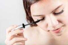 Woman applying black mascara on eyelashes with makeup brush Stock Photography