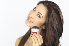 Woman applying blush. With a brush on her face Stock Image