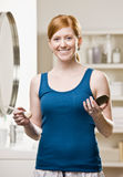 Woman applying blush with makeup brush Stock Images