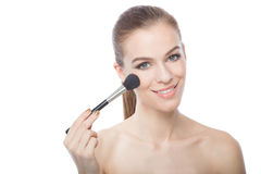Woman applying blush, on white background Royalty Free Stock Images