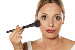 Woman applying blush. Young beautiful woman applying blush Royalty Free Stock Images
