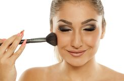 Woman applying blush. Young beautiful woman applying blush with a brush Royalty Free Stock Images