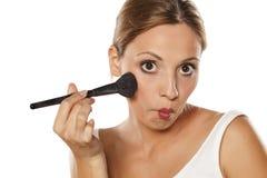 Woman applying blush Royalty Free Stock Photography