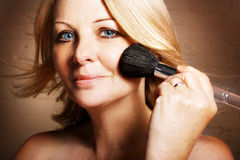 Woman applying blusher Stock Photos
