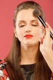 Woman applying blusher Royalty Free Stock Image