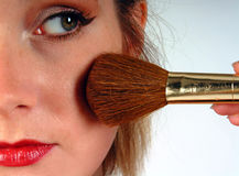 Woman applying blusher. Close up of a young womans face as she puts on blusher using a make up brush stock photography