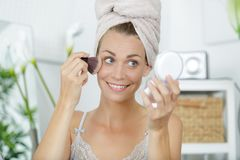 Woman applying blusher looking in compact mirror stock photo