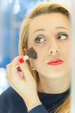 Woman applying blusher. In the mirror Stock Image