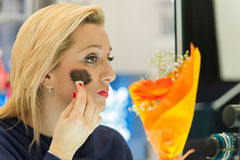 Woman applying blusher. In the mirror Stock Photos