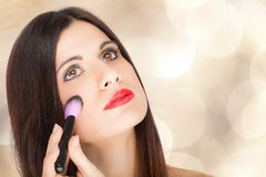 Woman applying blusher Stock Photography