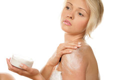 Woman applying body cream Stock Image