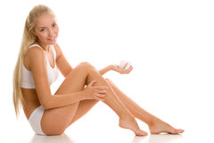 Woman applying body lotion Stock Images
