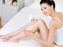 Woman applying body lotion on her legs. Young beautiful woman applying body lotion on her attractive legs - indoors Royalty Free Stock Image