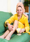 Woman applying body lotion to legs Royalty Free Stock Photos