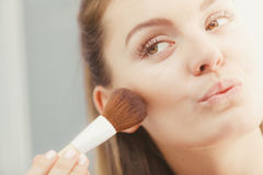 Woman applying bronzing powder with brush to her skin Stock Photography