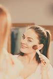 Woman applying bronzing powder with brush to her skin Stock Photography