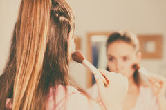 Woman applying bronzing powder with brush to her skin Royalty Free Stock Photos