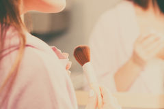 Woman applying bronzing powder with brush to her skin Royalty Free Stock Photo