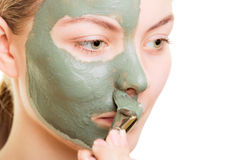 Woman applying with brush clay mud mask her face Royalty Free Stock Images